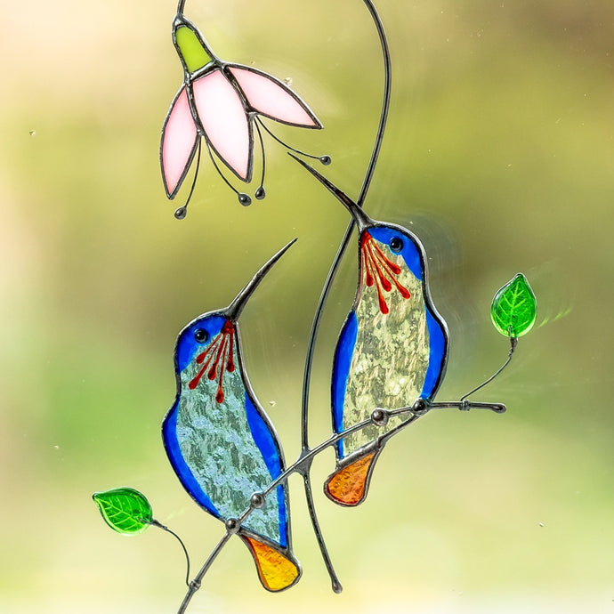 Zoomed stained glass blue hummingbirds on the branch suncatcher
