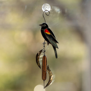 Window hanging of a stained glass red-winged blackbird on the reeds