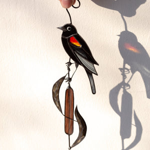 Suncatcher of a stained glass blackbird sitting on the reeds