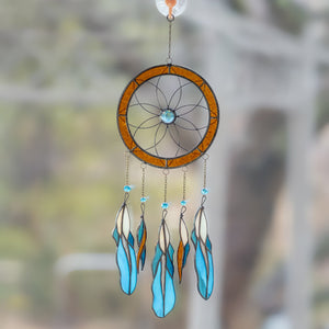 Dreamcatcher of stained glass with blue feathers hanging down