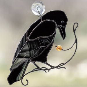 Zoomed stained glass raven on the branch with berry suncatcher for window