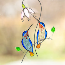 Load image into Gallery viewer, Stained glass pair of hummingbirds from light blue and clear glass sitting on the branch with pink flower above suncatcher
