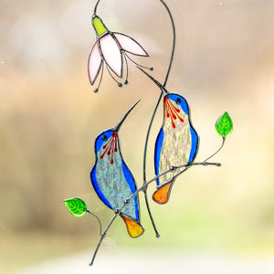 Stained glass pair of hummingbirds from light blue and clear glass sitting on the branch with pink flower above suncatcher