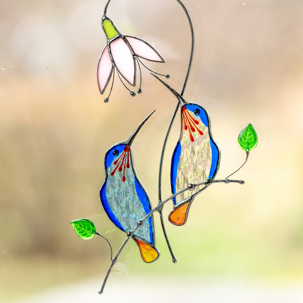Blue stained glass hummingbirds sitting on the branch with pink flower window hanging