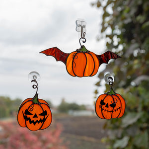 Stained glass suncatchers of two orange curved pumpkins and a flying one
