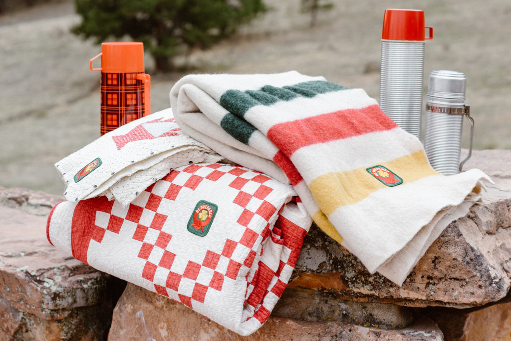a vintage red and white checked cotton quilt and green, red yellow striped wool blanket displayed on a rock with vintage thermoses