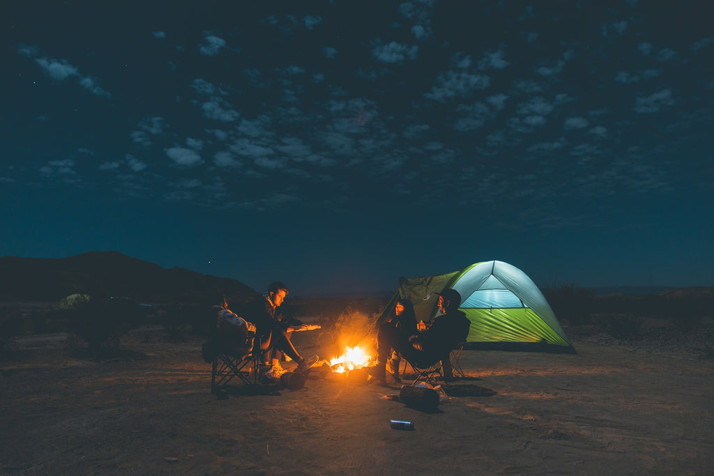 4 people sit around a camp fire in Big Bend National Park Texas USA