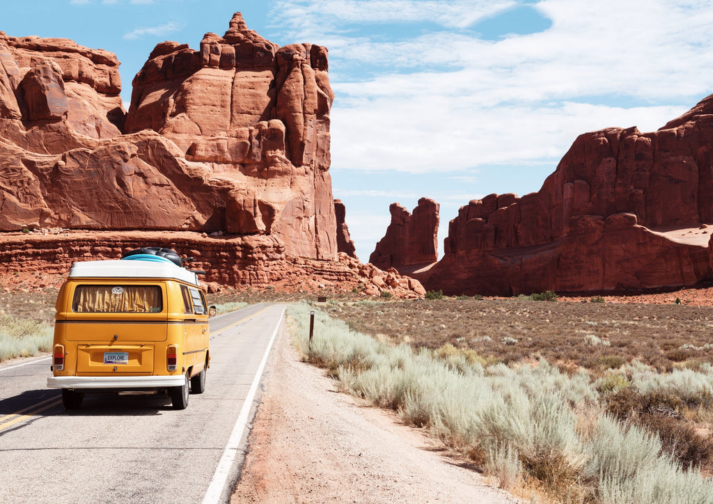 a yellow VW camper van travels down a road in Arches National Park Utah USA