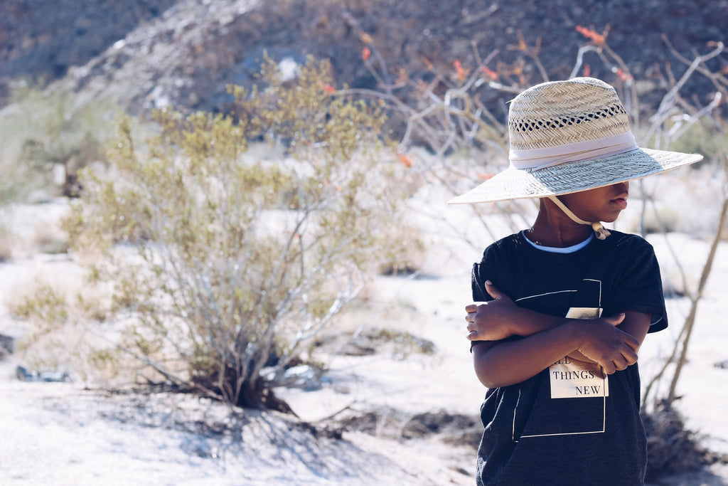 a young boy wears a straw hat at Joshua Tree National Park in California