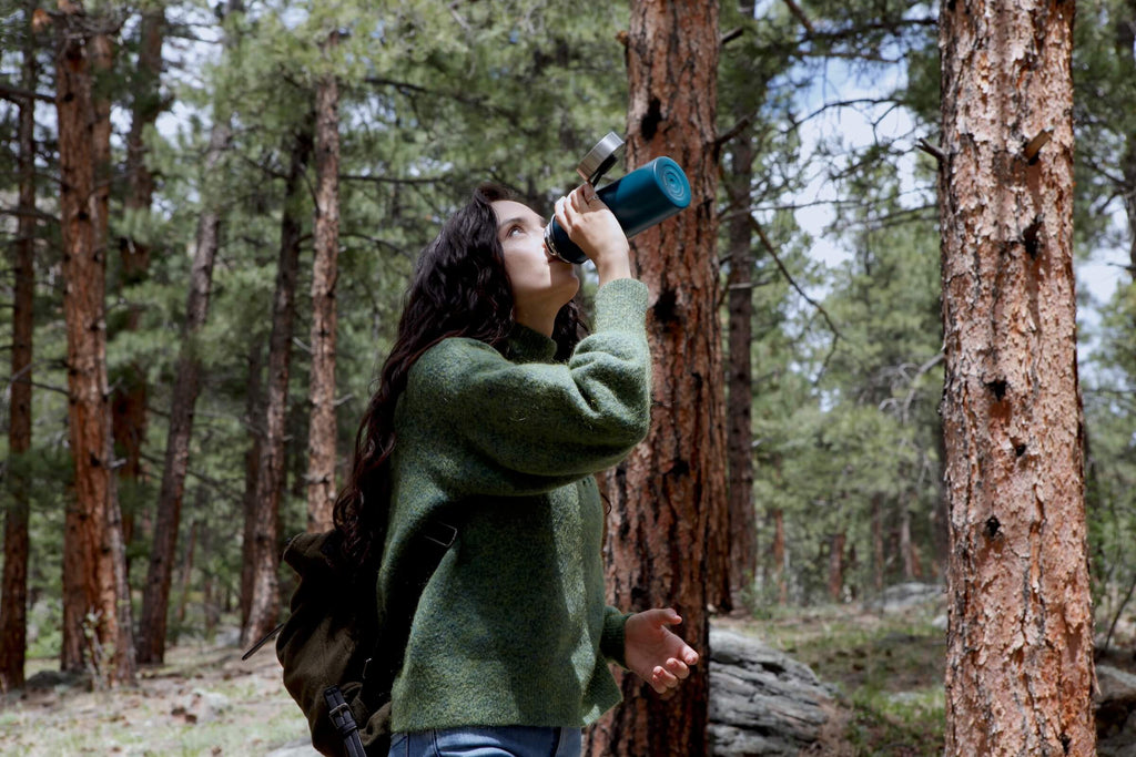 a young woman drinks from a water bottle while walking through the forest. she is practicing forest bathing.