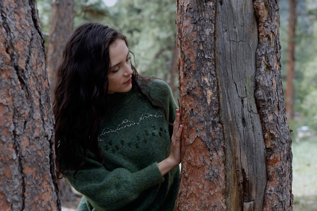 a young woman examines bark on a pine tree while practicing forest bathing.