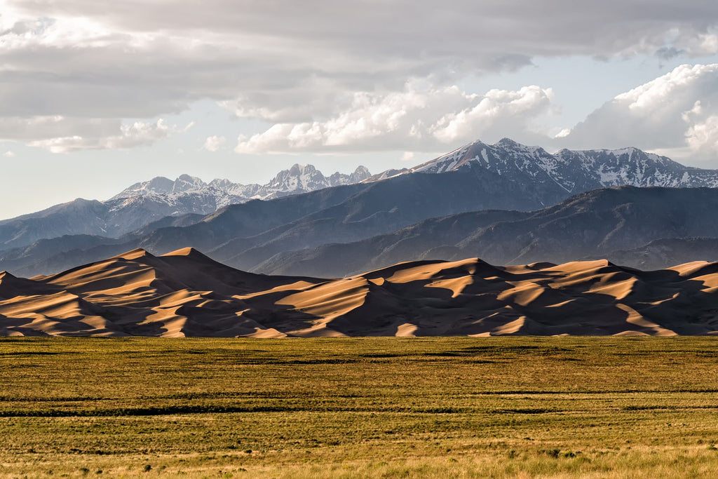mountains made of sand with snowcapped mountains in the background at Great Sand Dunes National Park Colorado