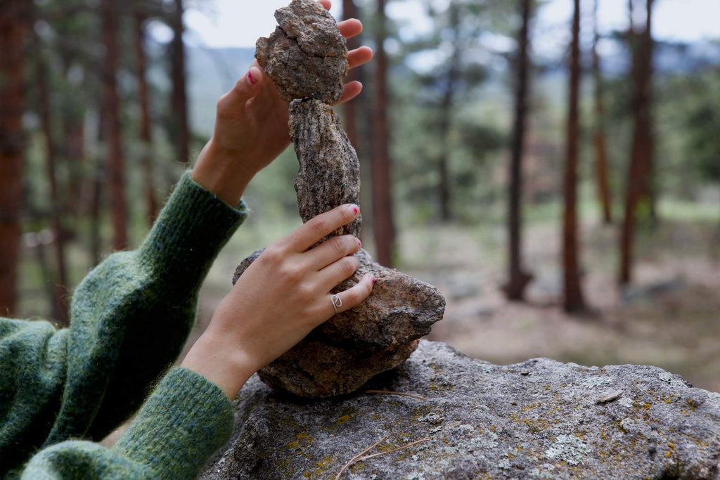 Hands balance a small rock on top of other rocks to make a cairn