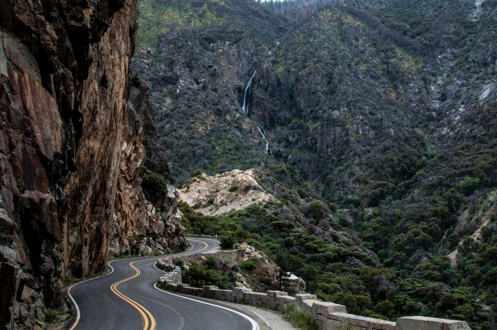 a winding road travels through rock canyons in Kings Canyon National Park California USA