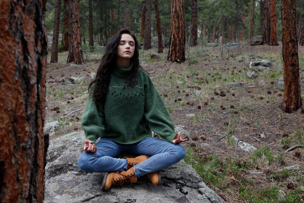 a young woman sits meditating on a rock in the forest. her eyes are closed. her legs are crossed. her palms are placed upward on her knees. she is forest bathing.