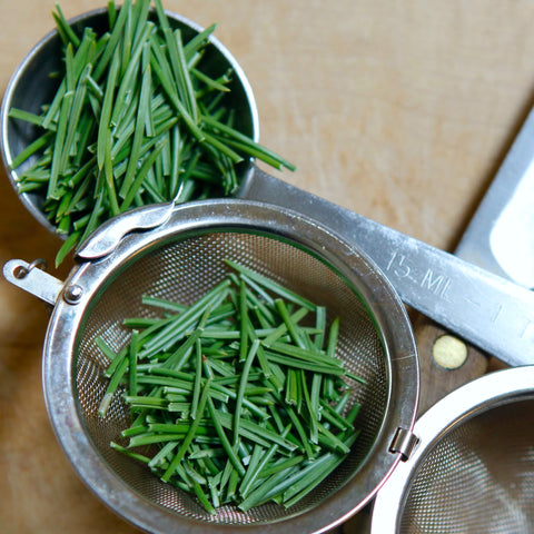Chopped pine needles in a tea strainer next to pine needles in a Tablespoon. 2 Tablespoons full of chopped pine needles