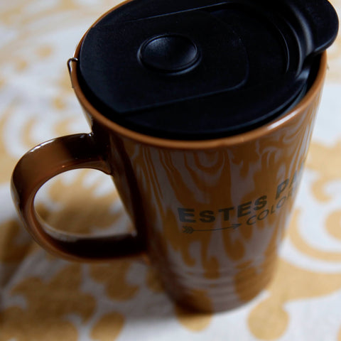 Pine cone tea steeps in a mug with a lid