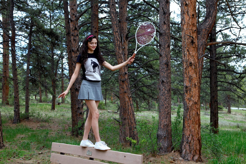 A young woman balances standing on the back of a park bench while holding a tennis racket