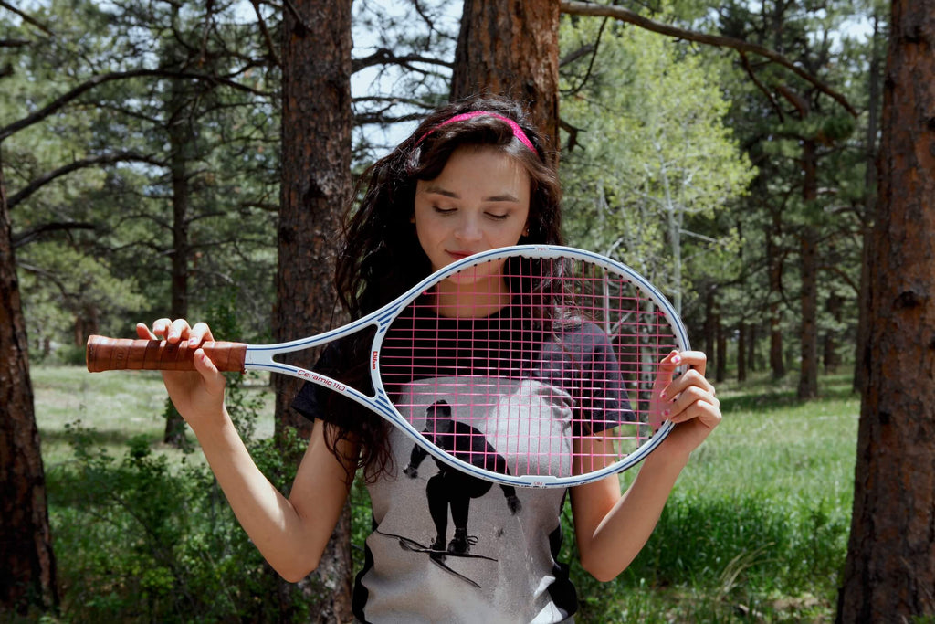 Trapper of Colorado vintage photo ski jumper black t-shirt worn by a young woman holding a tennis racket