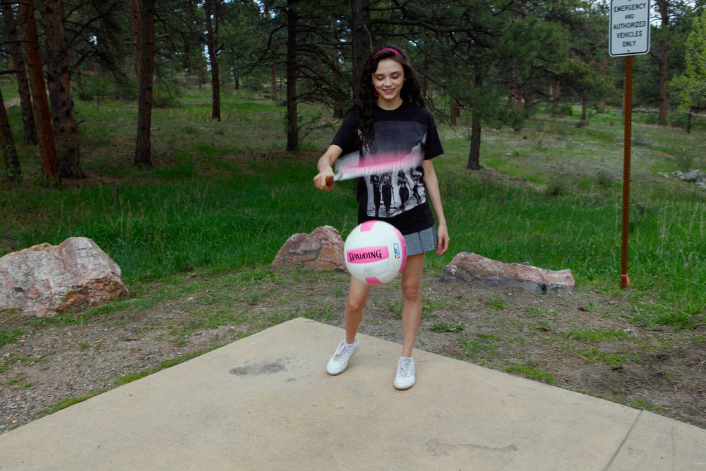 Trapper of Colorado California Ski Girls vintage photo t-shirt worn by a young woman bouncing a volleyball with a tennis racket