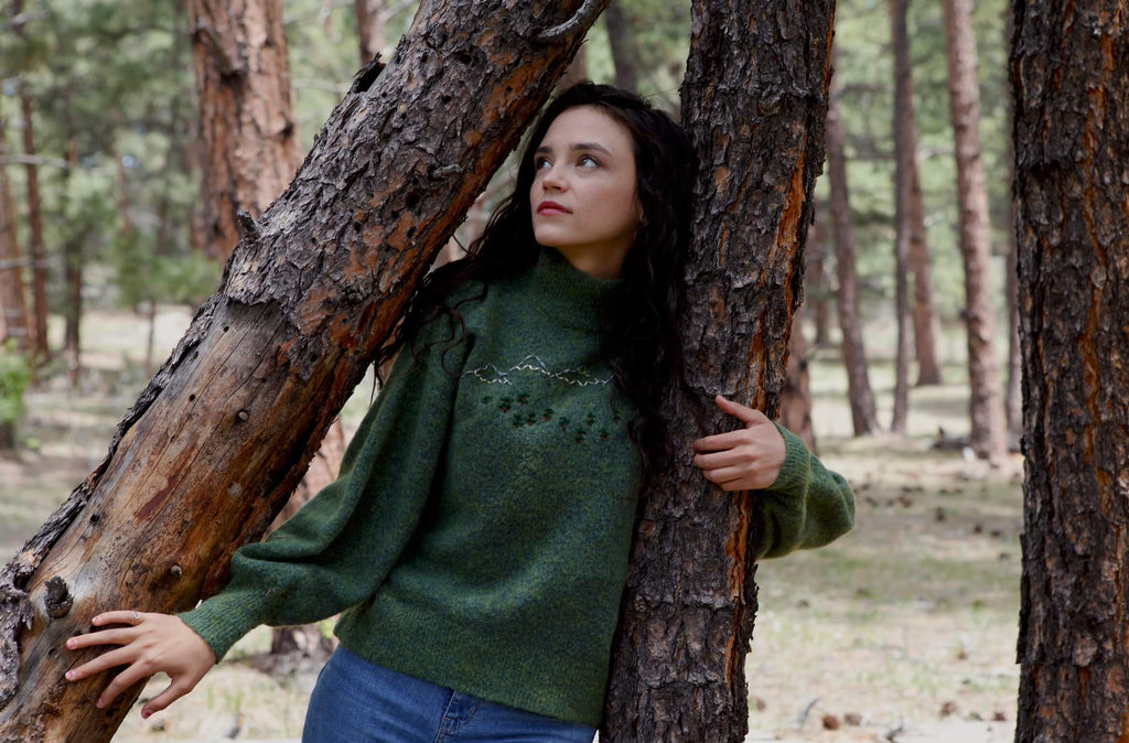 a young woman stands between two trees, touching them and looking upward