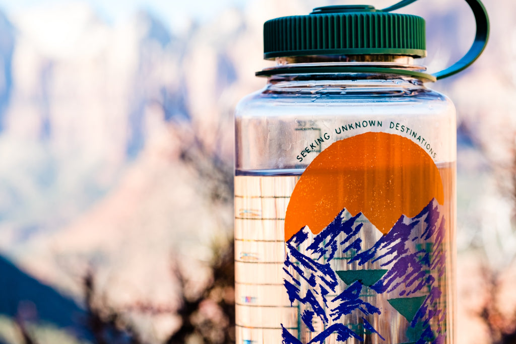 a water bottle with pictures of mountains is at Zion National Park in Utah USA