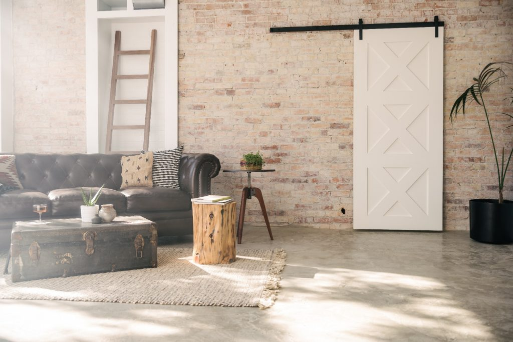 living room with brick accent wall and white barn door decoration
