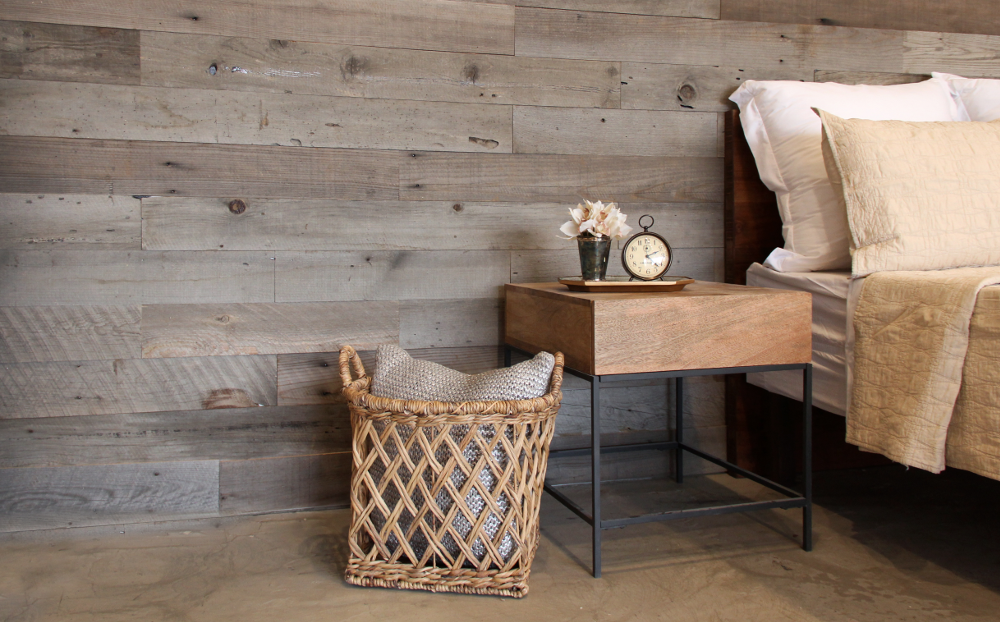 bed with bed stand sitting against a wood accent wall