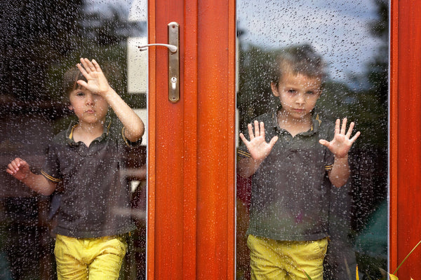 Two little boy, wearing same clothes looking through big glass