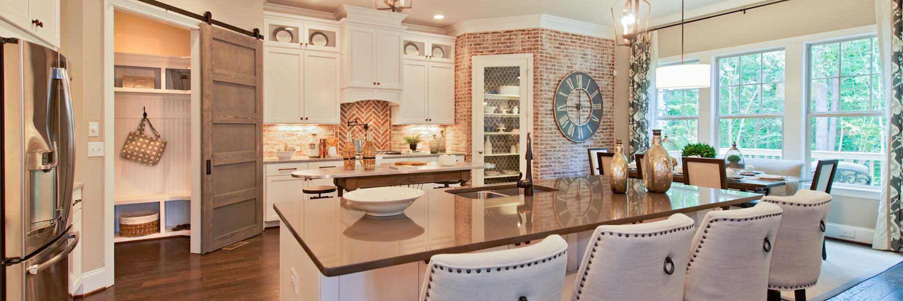 beautiful kitchen with countertops, cabinets, and brick accent walls