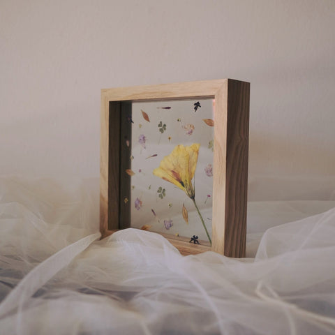 Florapeutic Mother's Day Floral design. A wooden frame contains a delicate design of pressed flowers.