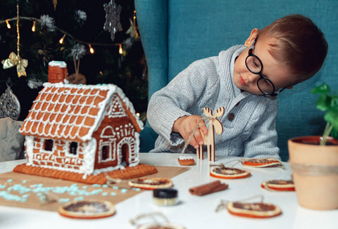 Boy decorates gingerbread house