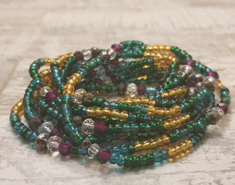 As a tribute to the beautiful Peacock, this custom piece consists of various hues of blue, purple, and gold with accented stones to achieve the ideal look.   In various cultures and mythologies, the peacock symbolizes self-confidence, protection from illness and misfortune as well as holiness and hope.  This waist bead is created on a stretchy cord for convenience and durability.