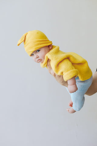 baby-wearing-yellow-sweater-and-hat-being-held-by-one-hand-first-year-of-motherhood.jpg