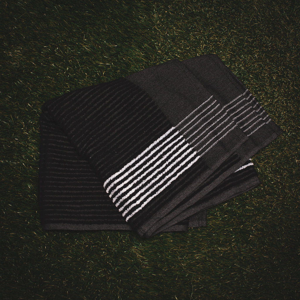Black Caddy Towel with white stripes from cayce golf laying on the grass