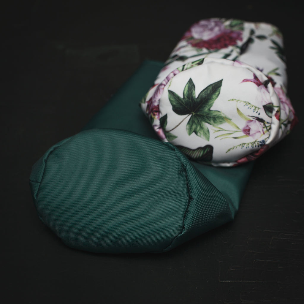 a forest green driver headcover with a floral fairway wood cover laying on top of it