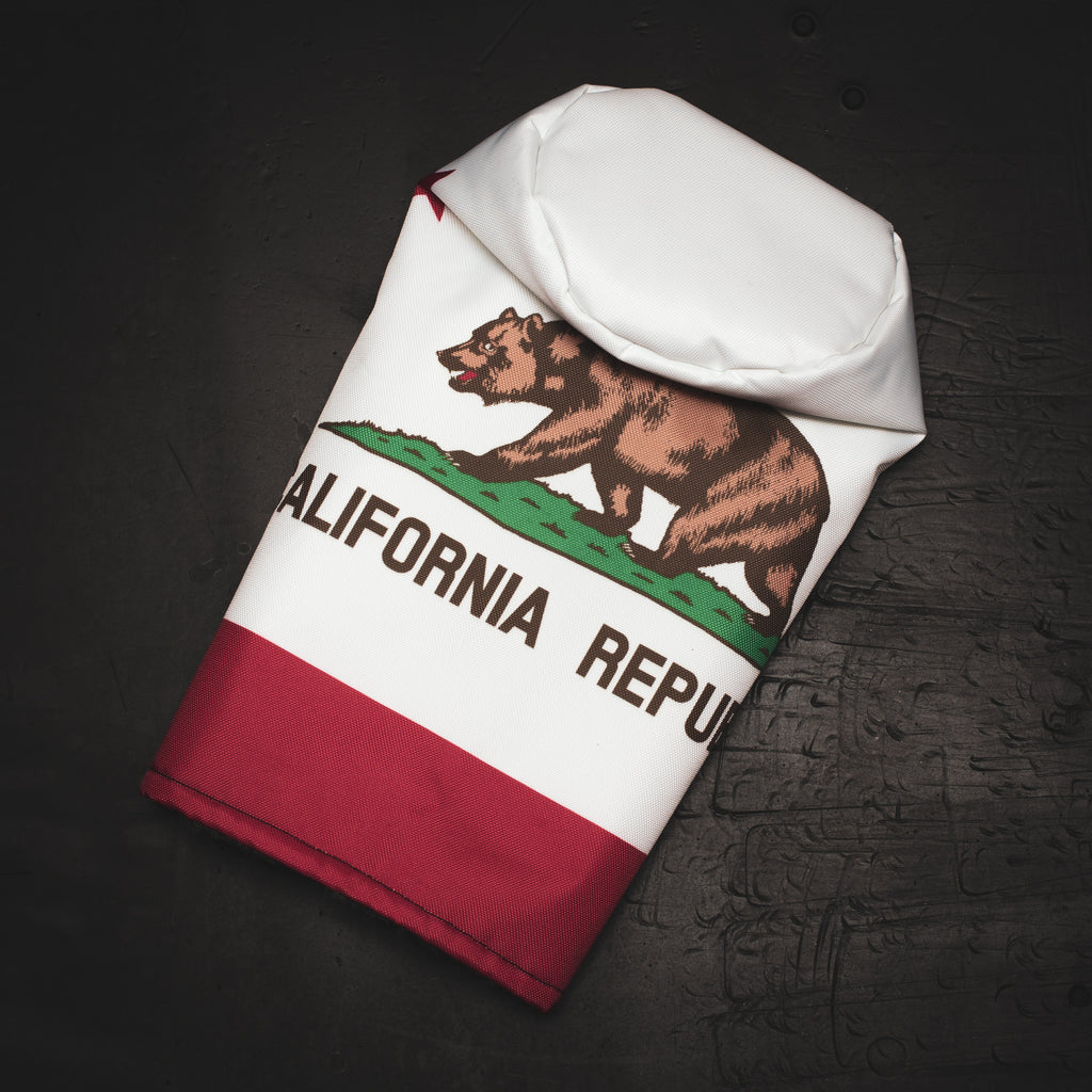 Golf headcover featuring the California State Flag design laying on a black desk (4756387168335)