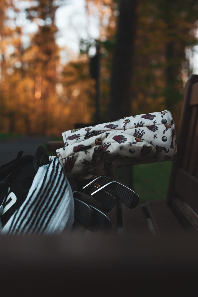 golf bag laying on a bench with Chubbs golf headcovers from Cayce golf
