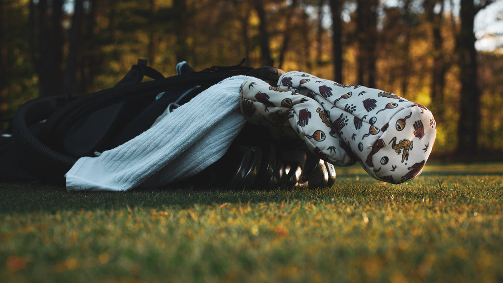 golf bag laying in the fairway with Chubbs themed golf head covers and caddy towel from Cayce golf