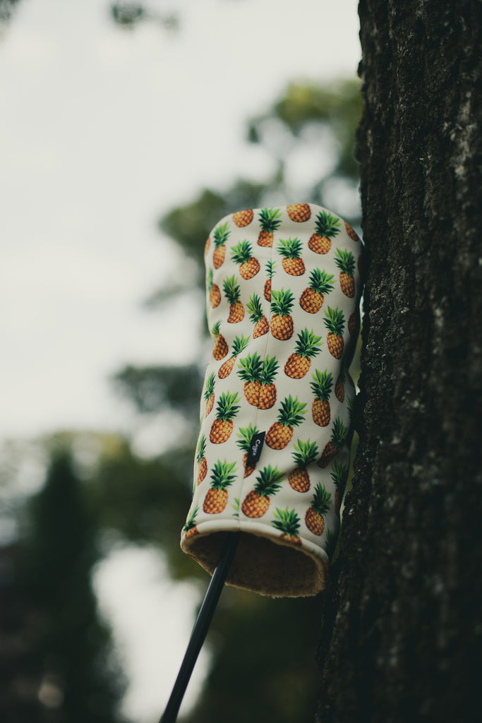 pineapple golf head cover leaning against a tree