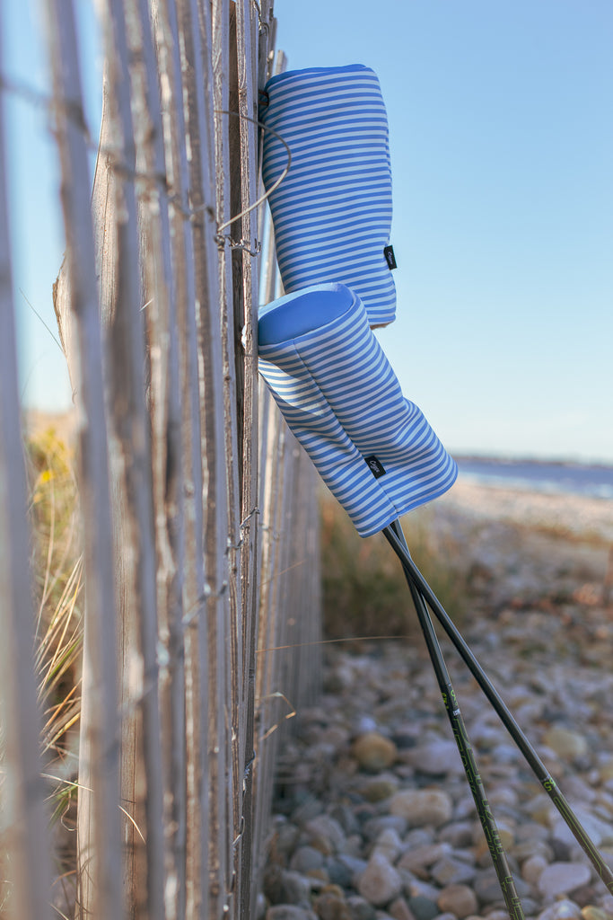 Seersucker golf headcovers leaning against a fence at the beach