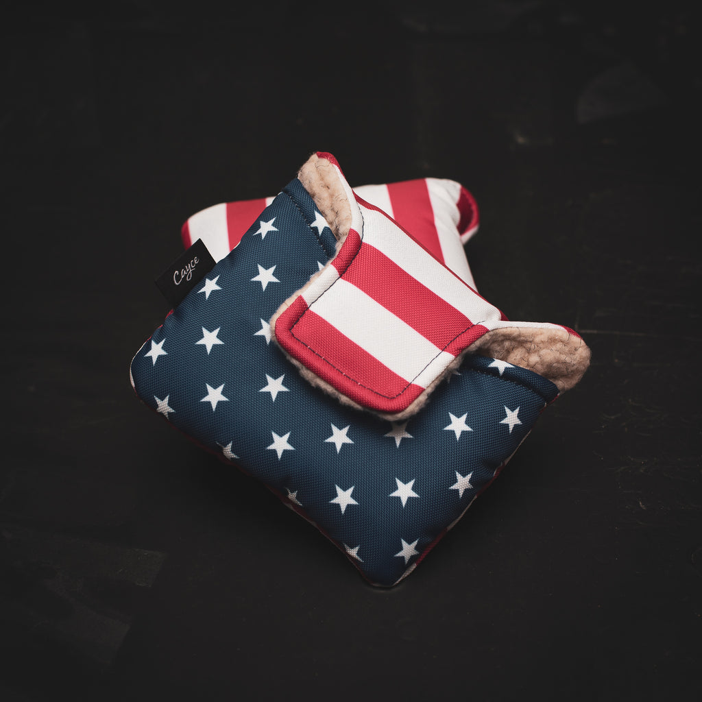 Two American Flag Mallet Putter Covers laying on a desk. The top side of the cover is striped and the bottom half has the stars.