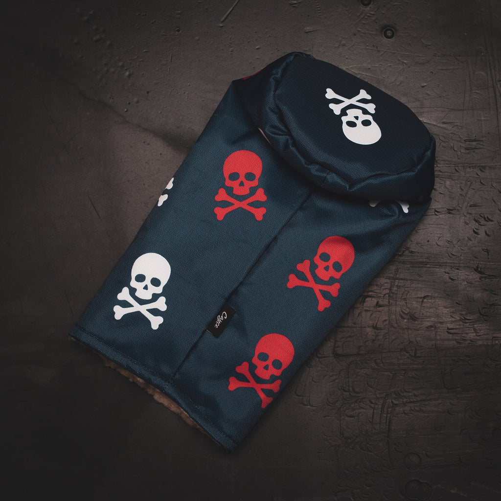 Red, white, and Blue skull and crossbones golf headcover laying on a desk (4126014472271)