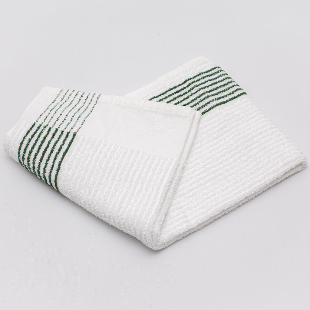 caddy towel with green stripes laying folded on a white background