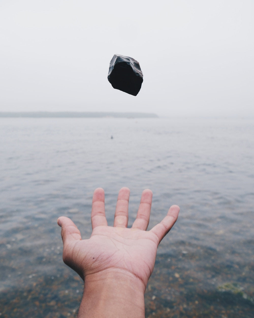 A hand throws Black Sardonyx in the air | Talsam, smart jewelry for couples