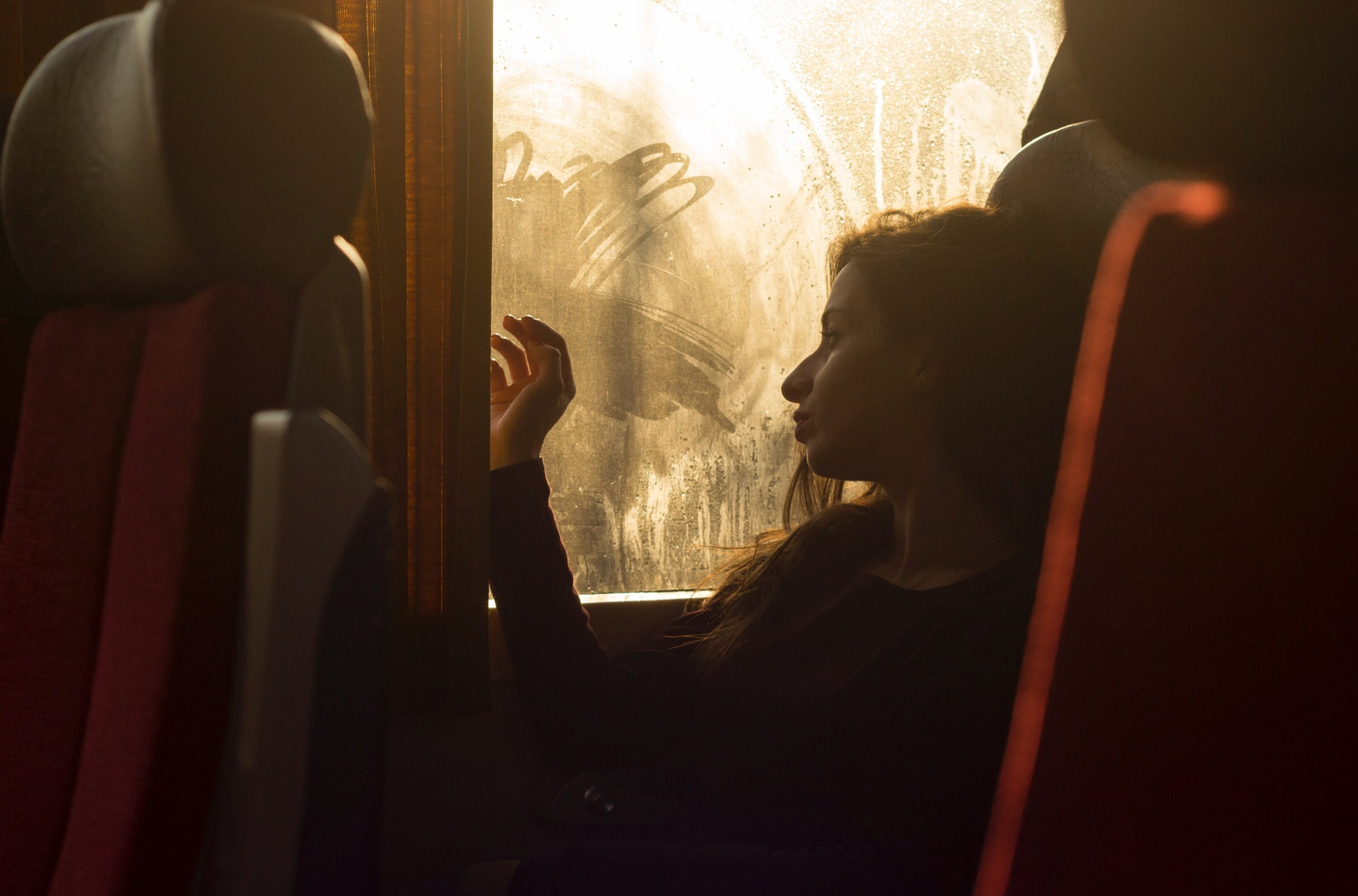 A brunette woman travels long-distance and looks through the window of a train with a nostalgic expression | Talsam