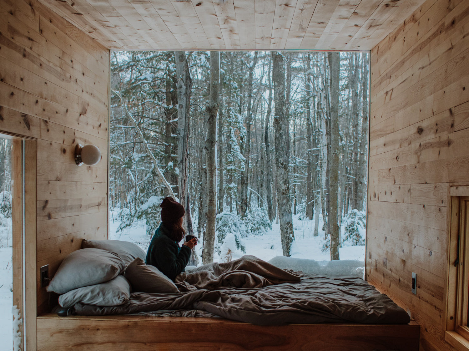 Girl looking out at snowy forest