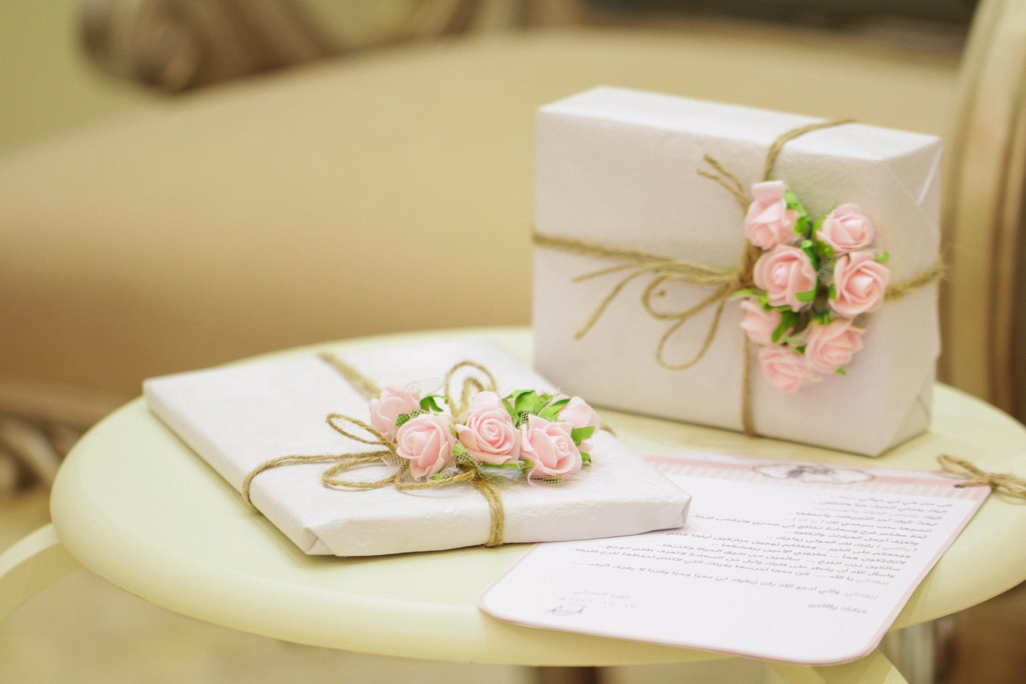 The Five Love Languages, Receiving Gifts: two boxes wrapped in white paper and pink roses, placed on a round coffee table | Talsam, smart jewelry