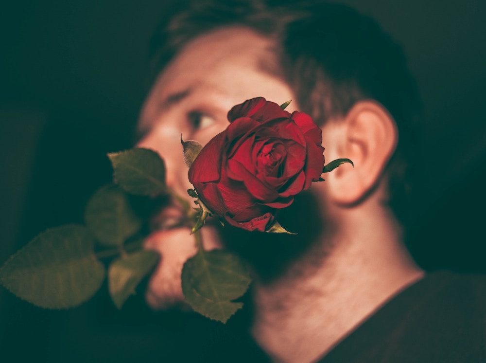 A creative way to send flowers to her work: a man holds a red rose on his mouth | Talsam, Smart Jewelry