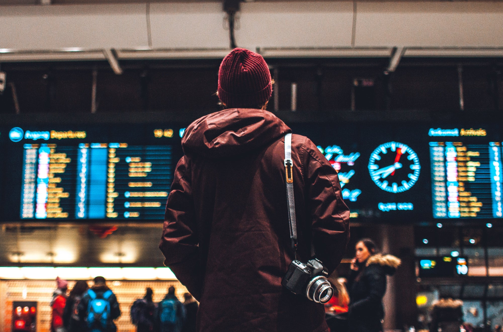 A person dressed in a long coat, a red cap, and a camera slung over the shoulder looks at the airport departures screen | Talsam